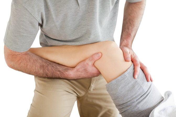 Мануальный терапевт осматривает колено