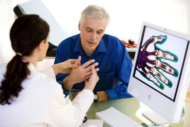 Врач осматривает пальцы руки