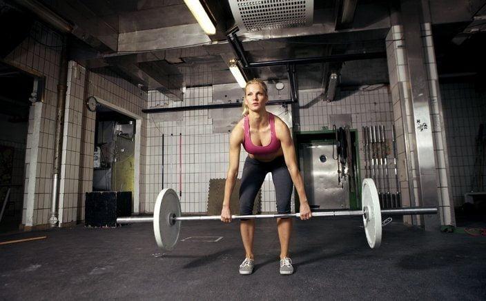 Женщина поднимает тяжести